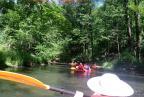 Spływ: osoby w kajakach na wodzie. Na pierwszym planie słomiany kapelusz