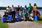 grupa uczestników zawodów na tle jeziora