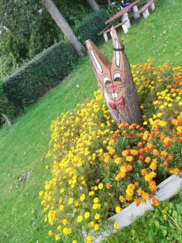 Stanica - figurka zająca wyrzeźbionego w pniu obrośnięta kwiatami