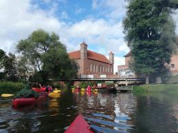 Spływ: widok kajaków na wodzie, w tle zamek w Lidzbarku Warmińskim